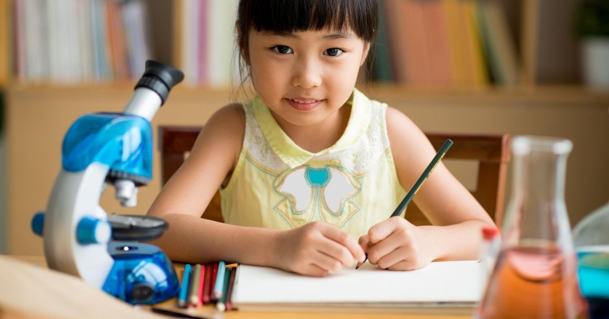 A young girl writes at a desk surrounded by scientific contraptions.