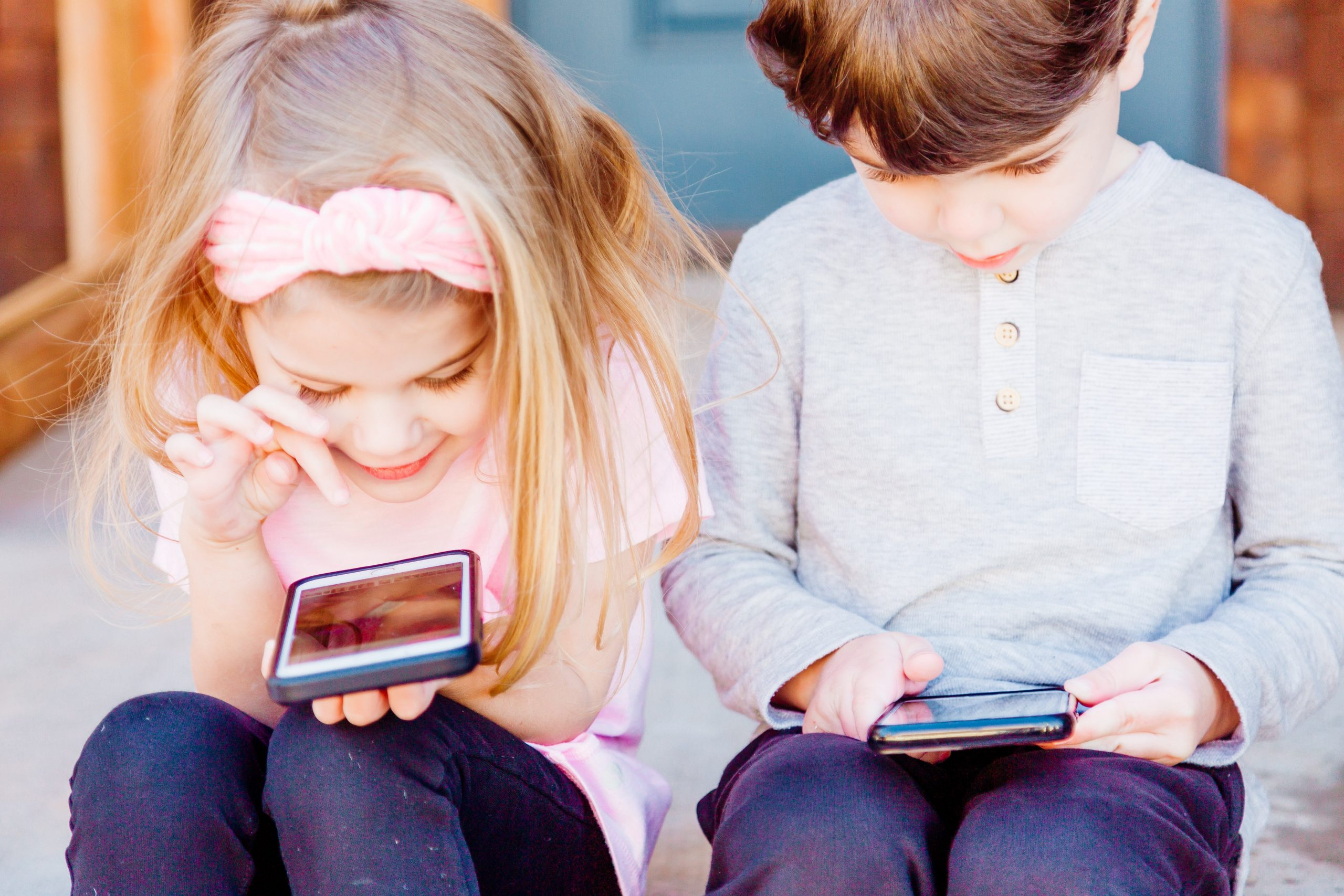 two children use mobile devices