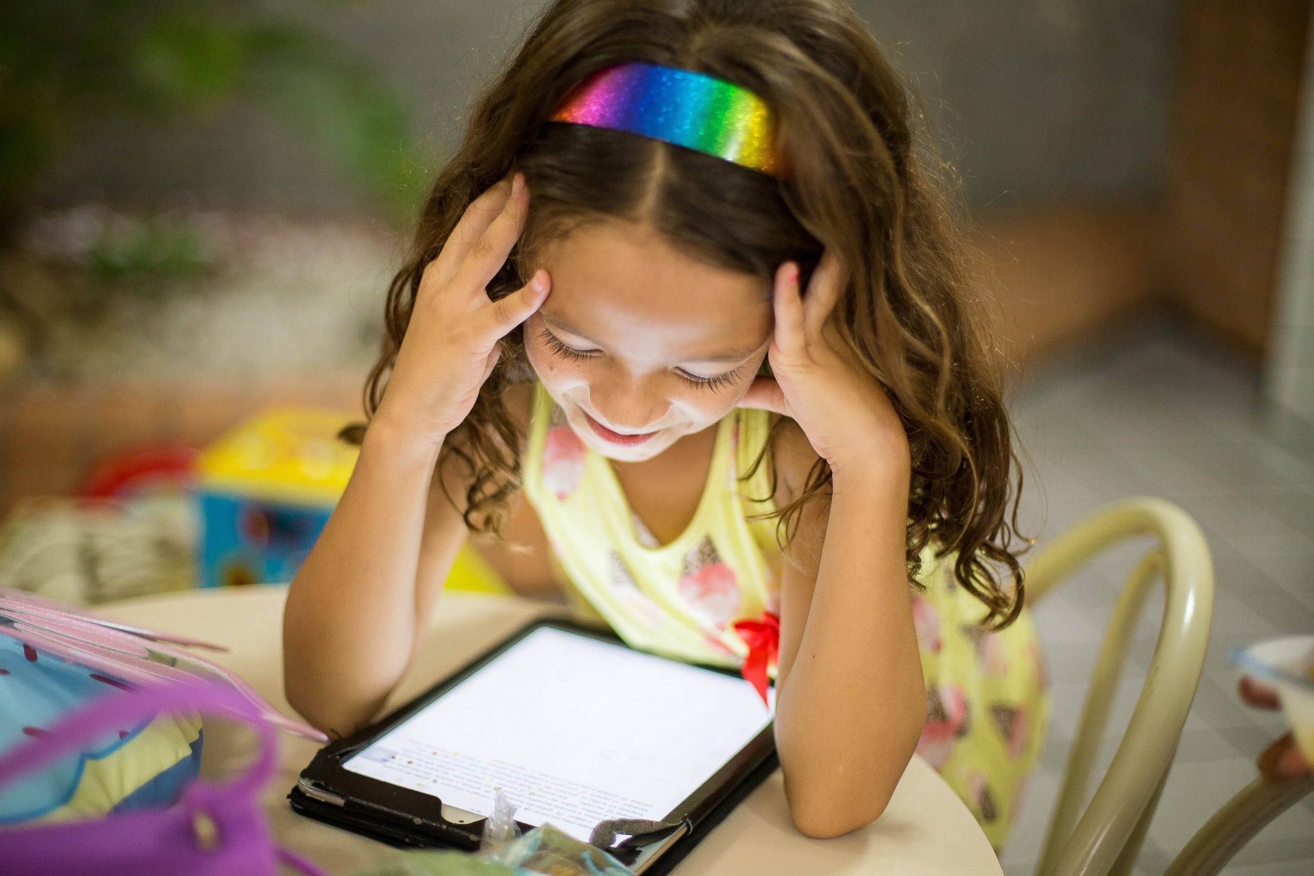 Child looks at a tablet