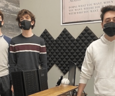 Three-young-men-with-masks-on-standing-in-recording-studio