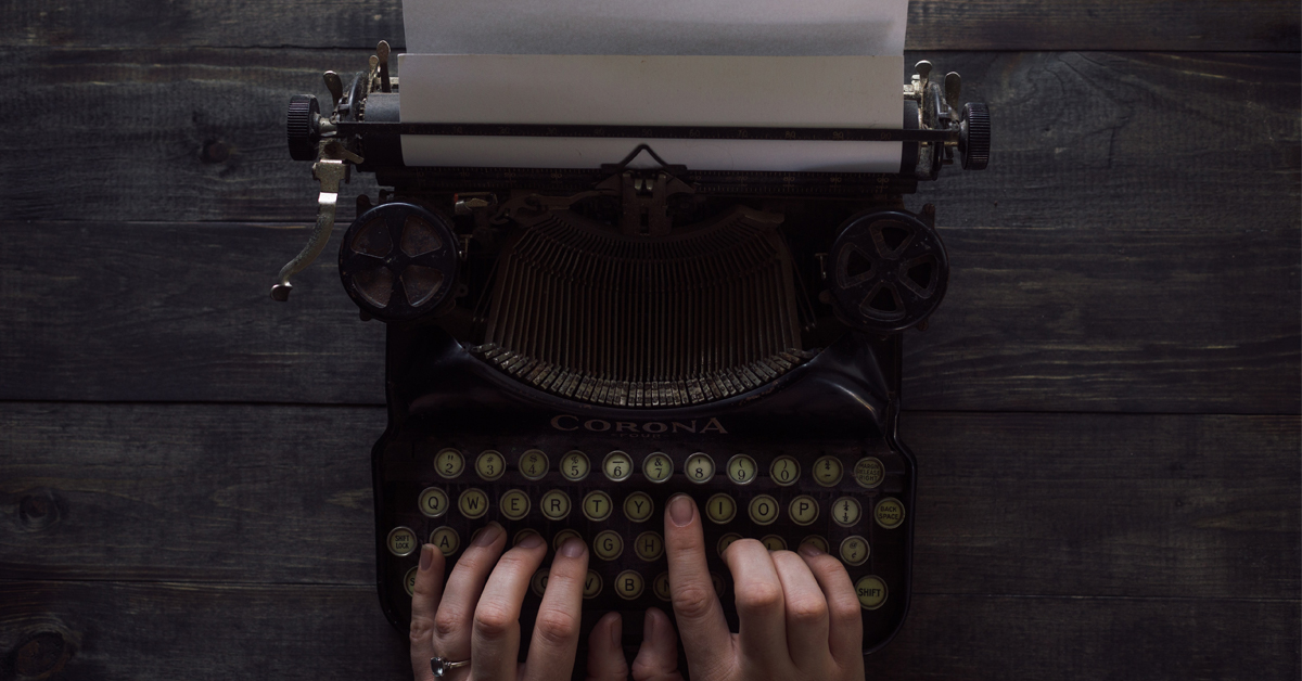 Hands are positioned on a typewriter's keys.